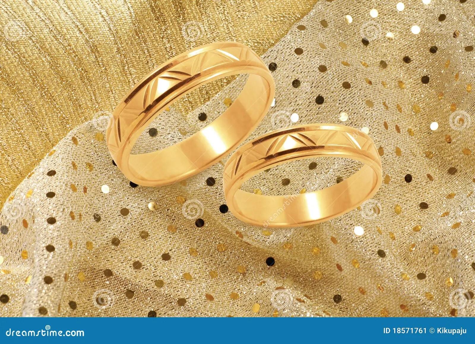 Gold Wedding Rings On Golden Festive Background Stock