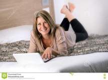 Gorgeous Mature Woman Laying Bed With Laptop Stock