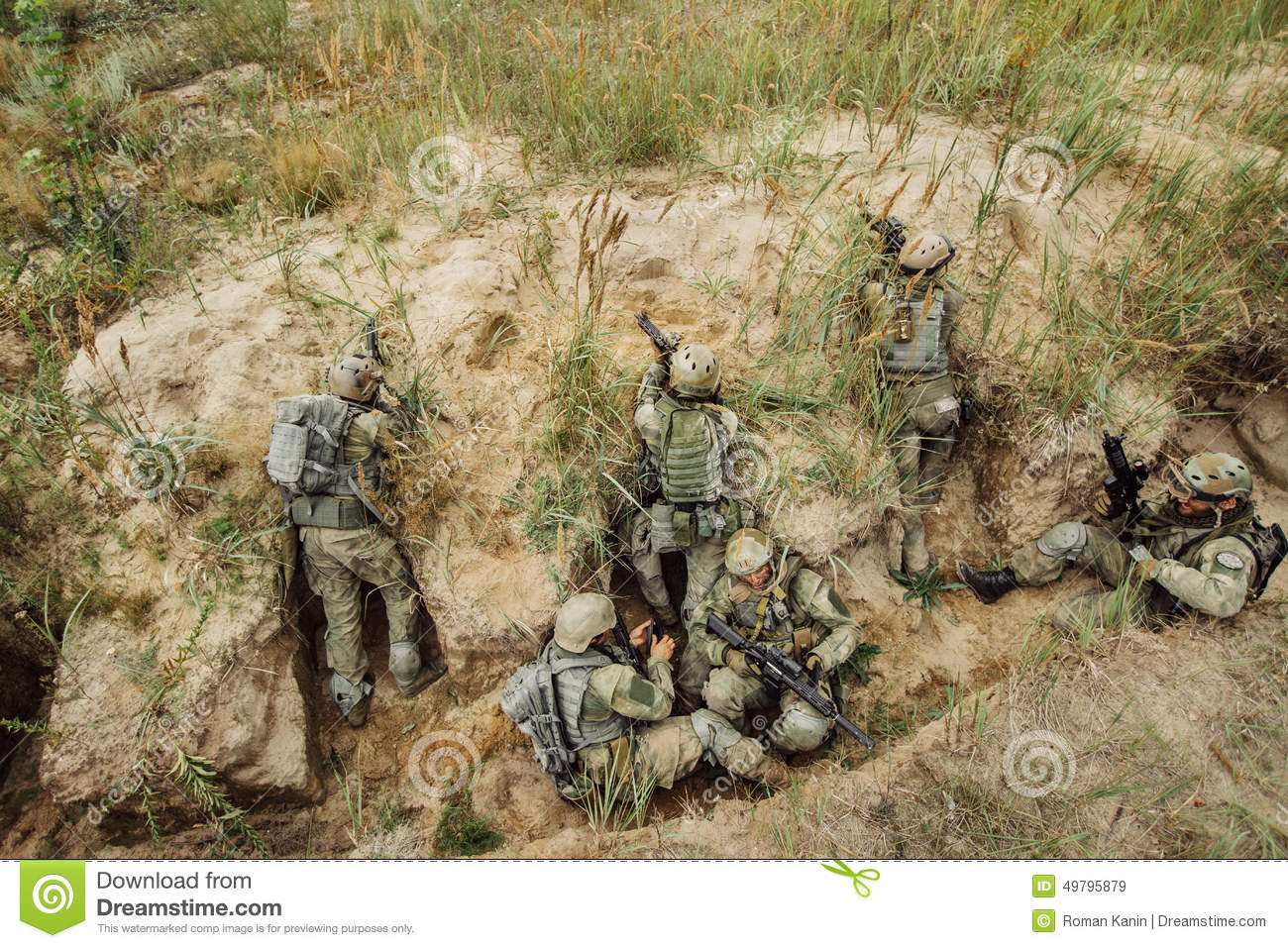 Group Of Soldiers Hiding In The Trenches And Firing Stock