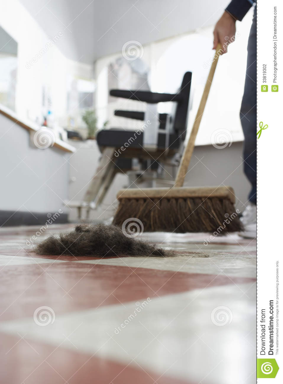 Hairdresser Sweeping Hair Clippings On Floor Stock Photo