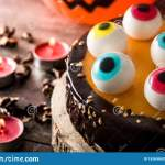 Halloween Cake With Candy Eyes Decoration On Wooden Table
