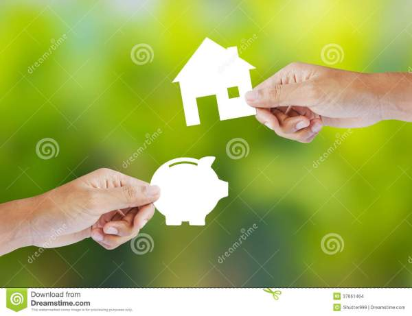Hand Holding Paper Piggy Bank And House Shape Stock