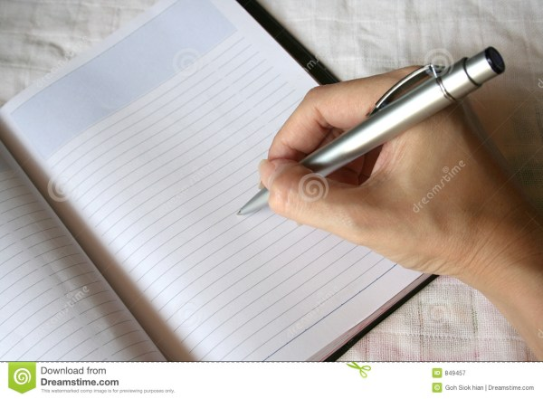 Hand Holding Pen Writing Note Book Stock