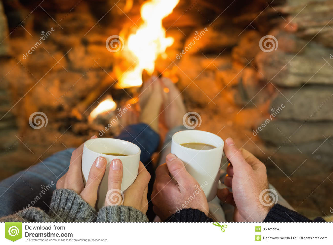 Couple Relaxing In Front Of Fireplace Man Looking At Woman Stock Hands Holding Coffee Cups In Front Of Lit Fireplace Stock