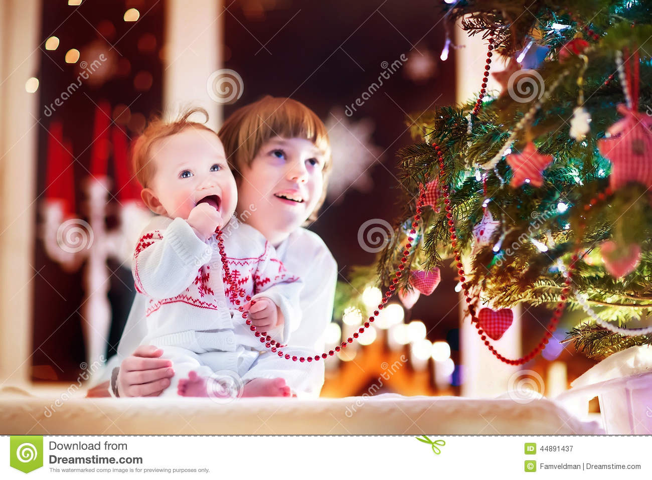 Happy Children Playing Under A Beautiful Christmas Tree