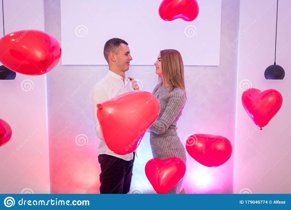 Download Happy Couple In Love Posing With Red Air Balloons In Shape ...
