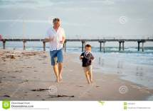 Happy Father Playing Beach With Little Son Running