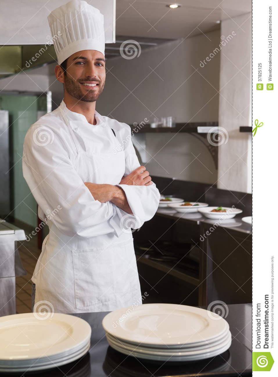 Happy Head Chef Standing With Arms Crossed Behind Counter