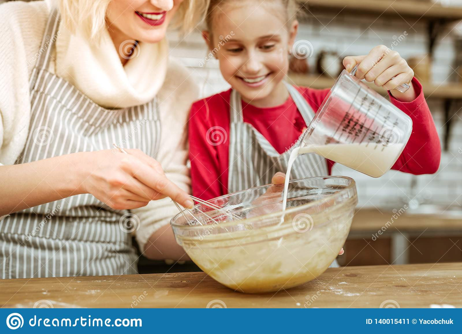Happy Joyful Little Kid Adding Milk From Measuring Cup