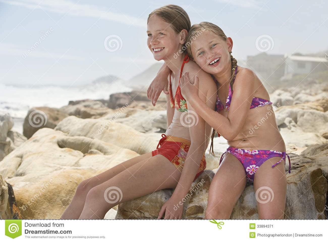 Happy Little Girl Sitting With Sister On Rocks Stock Image