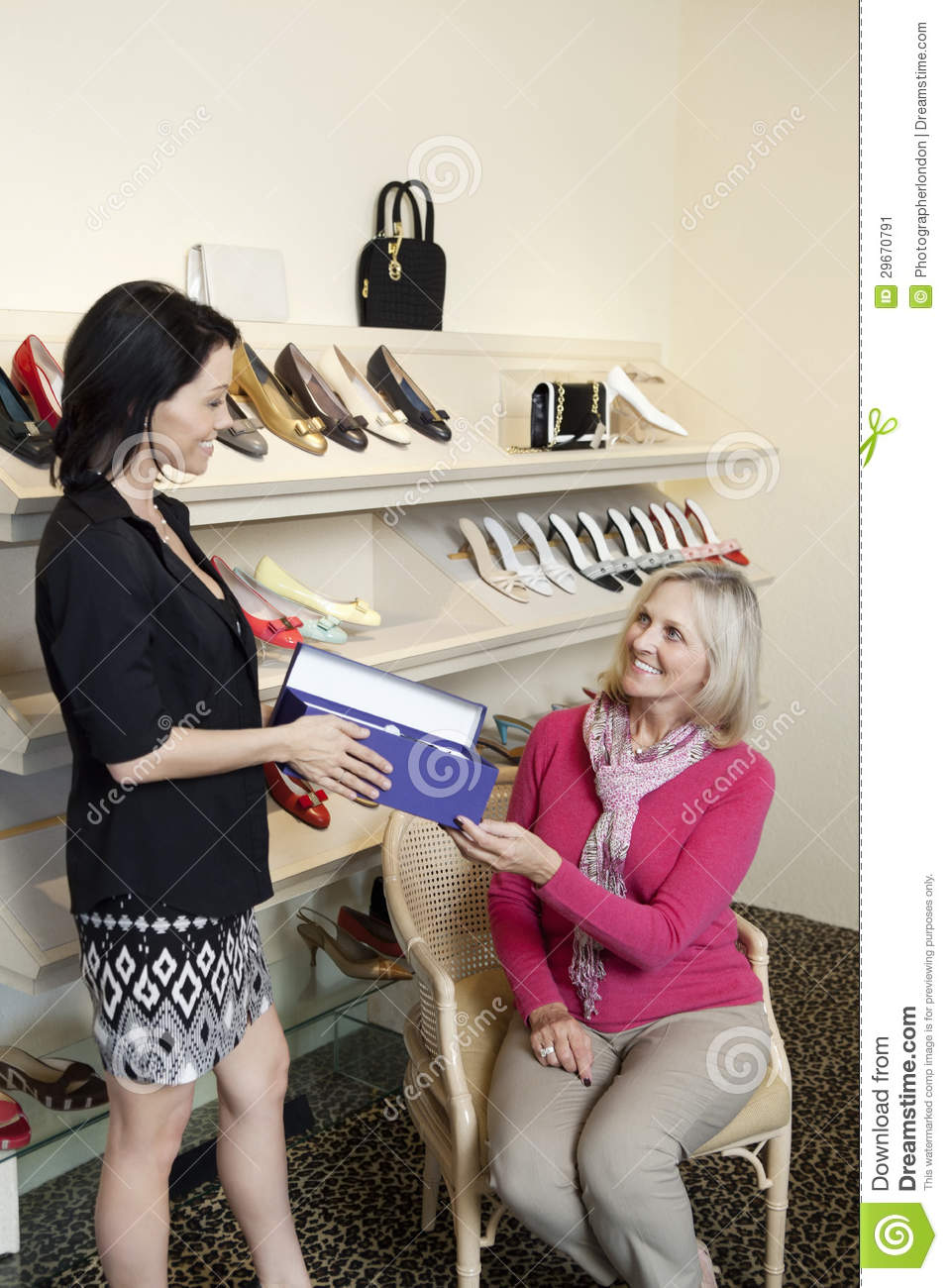 Happy Mature Customer Taking Footwear Box From Mid Adult Female Salesperson In Shoe Store Stock