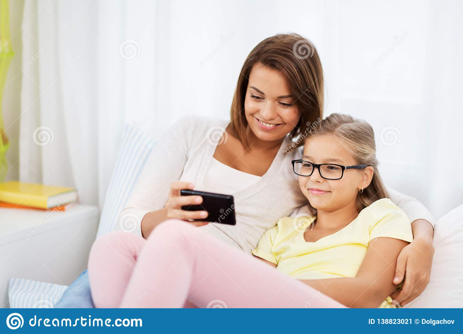 Happy Mother And Daughter With Smartphone At Home Stock
