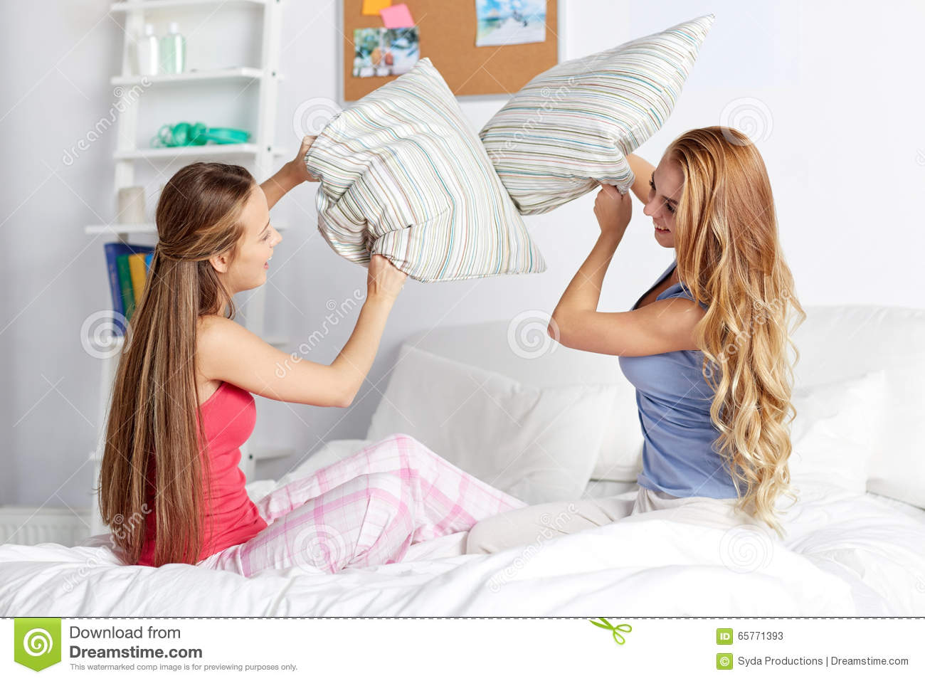Happy Teen Girl Friends Fighting Pillows At Home Stock