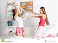 Happy Teen Girl Friends Fighting Pillows At Home Stock ...