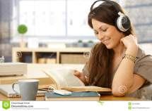 Girl with Headphones Reading Book Stock Image