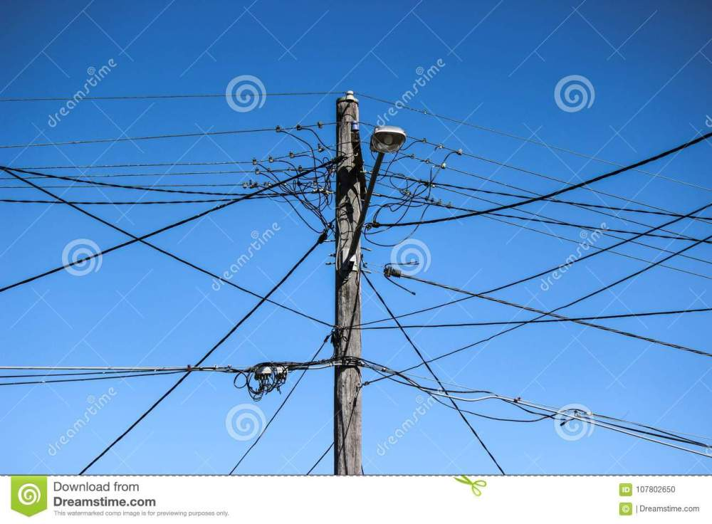 medium resolution of high voltage electricity pole with complex wiring street lamp and blue sky