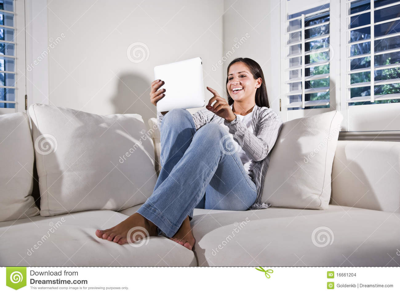 Hispanic Woman Using Tablet Computer On Couch Stock Images  Image 16661204