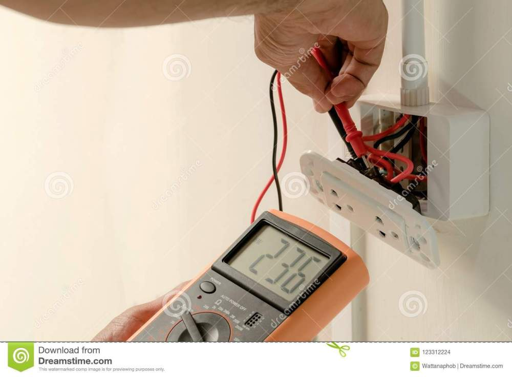 medium resolution of electrician is using a digital meter to measure the voltage at the power outlet in on the wall