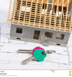 home keys and small house under construction lying on electrical drawings for project concept of building home [ 1300 x 957 Pixel ]