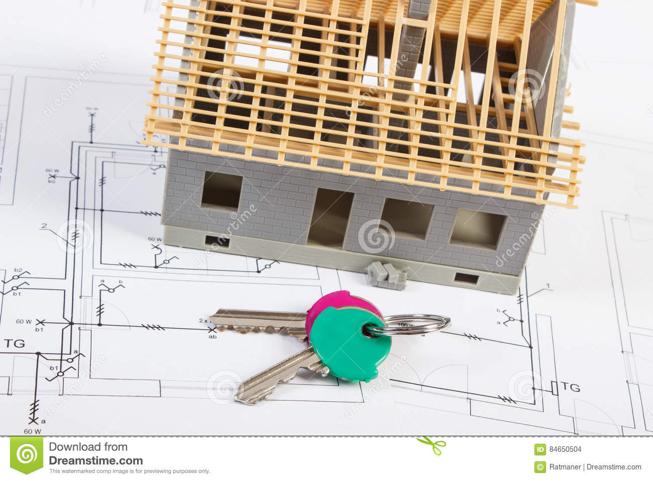 hight resolution of home keys and small house under construction lying on electrical drawings for project concept of building home