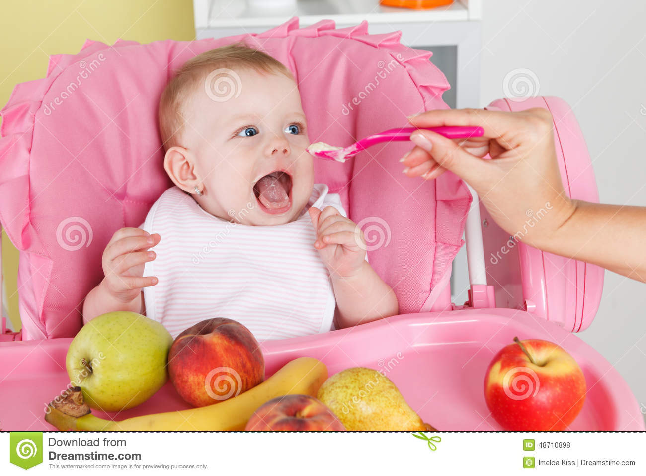 baby girl chair gray wicker hungry is feeded by mother stock photo image