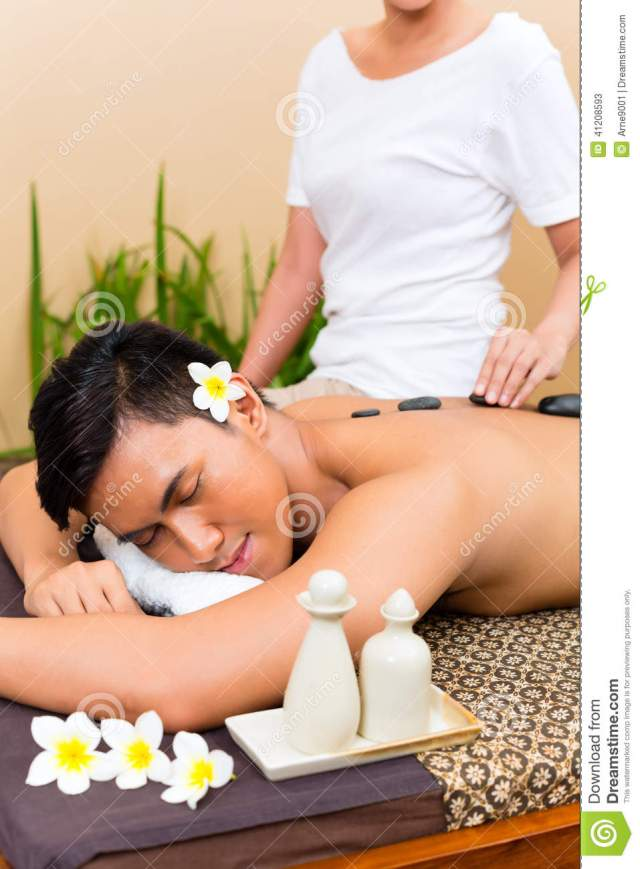 Indonesian Asian Men In Wellness Beauty Day Spa Having Hot Stone Massage Or Treatment Looking Relaxed