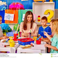Teacher Table And Chair Universal Covers Canada Kids With Woman Painting On Paper In Kindergarten . Stock Photo - Image: 67499102