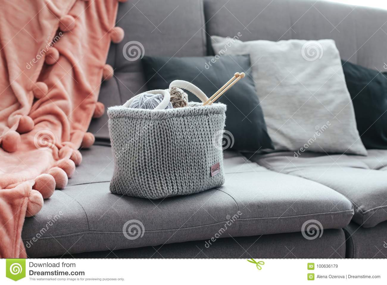 knitted basket with yarn and needles on grey sofa by the warm pompon blanket and cushions still life photo of nordic interior details cosy place in winter
