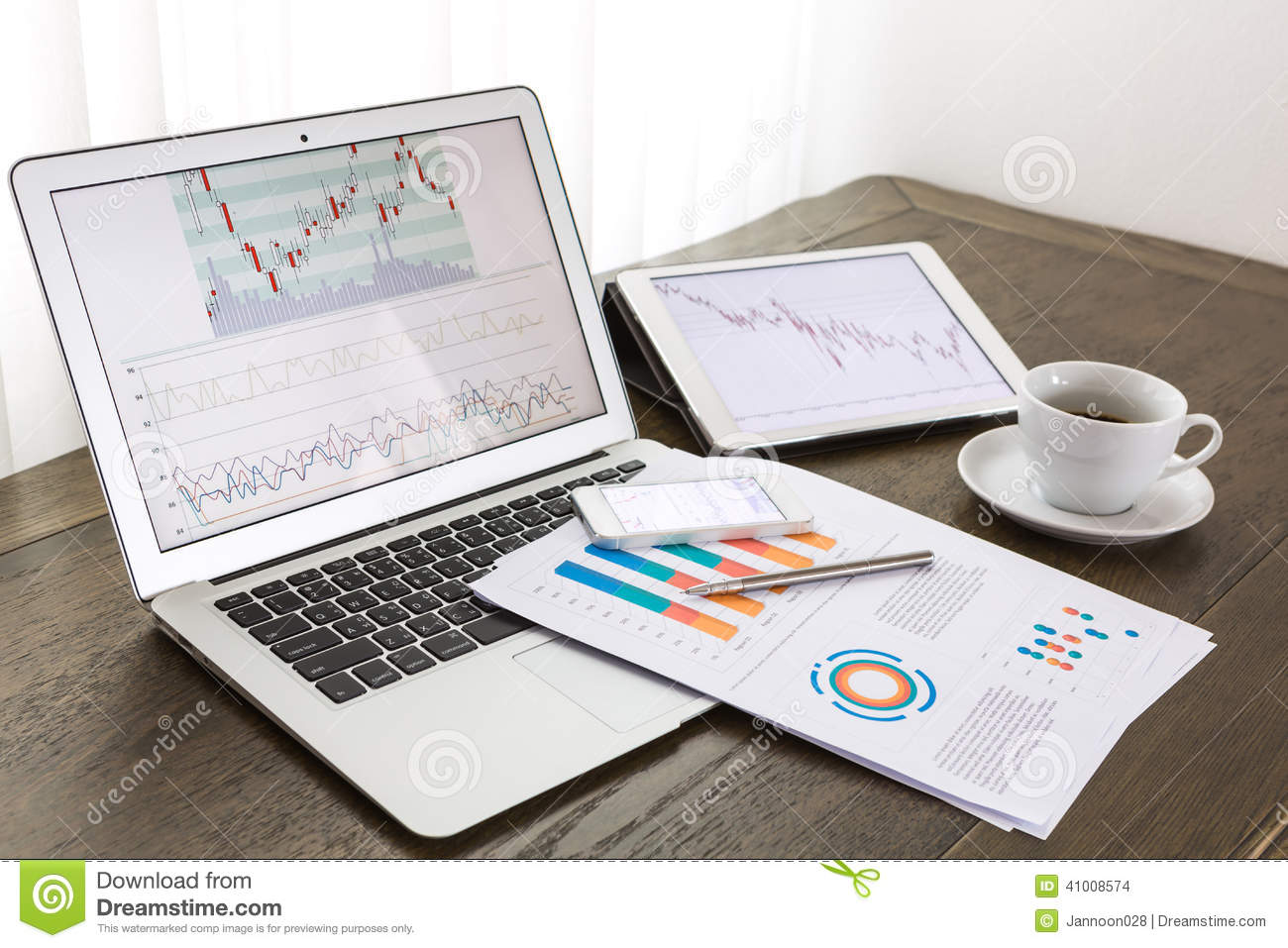 Laptop Tablet  Smartphone With Financial Documents Stock