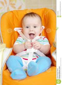 Laughing Baby Sitting On Babies Chair Age Of 6 Month Stock ...