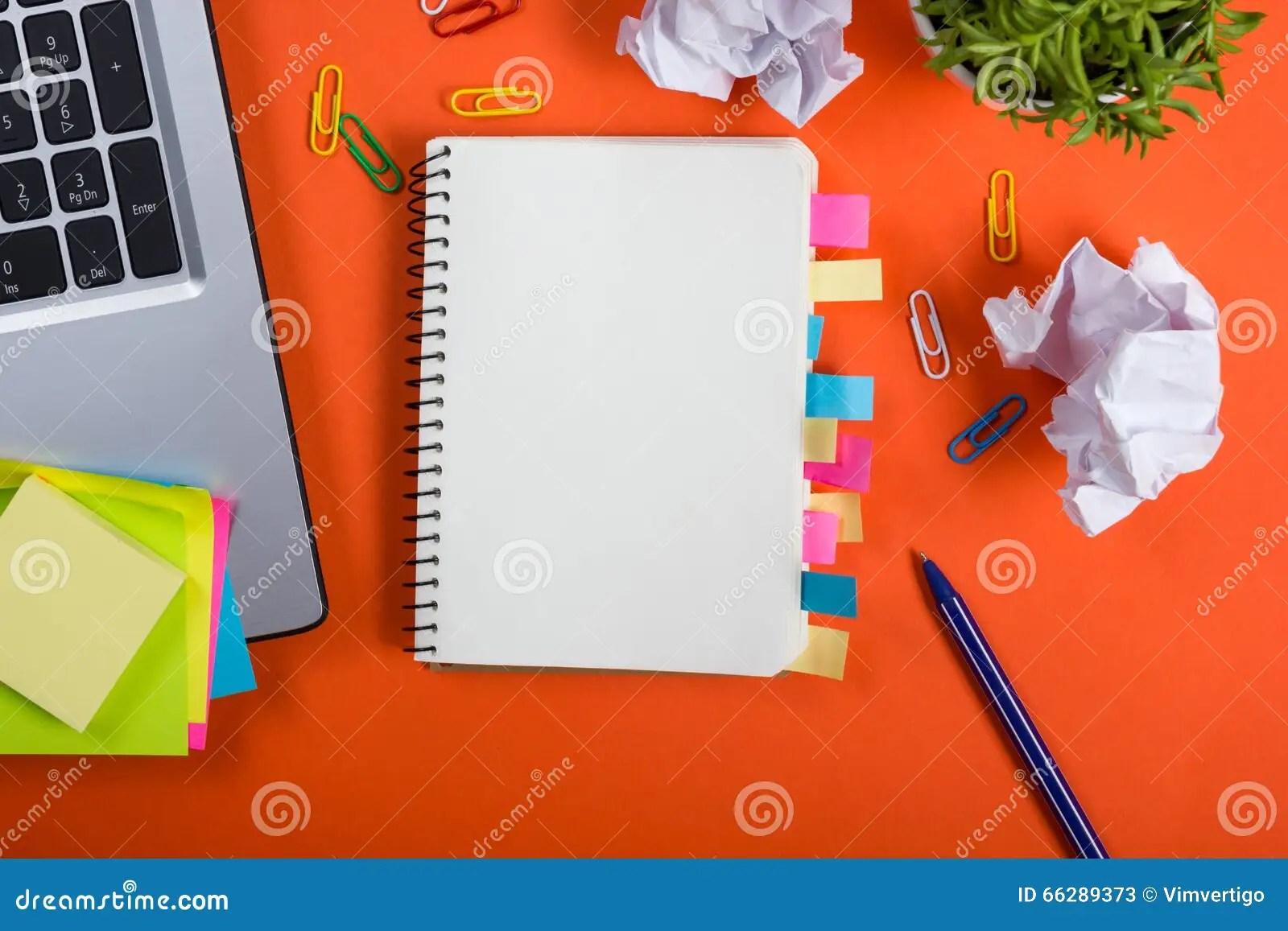 le bureau de table de bureau avec l ensemble d approvisionnements colores bloc notes vide blanc tasse stylo pc a chiffonne le papier fleur sur le fond