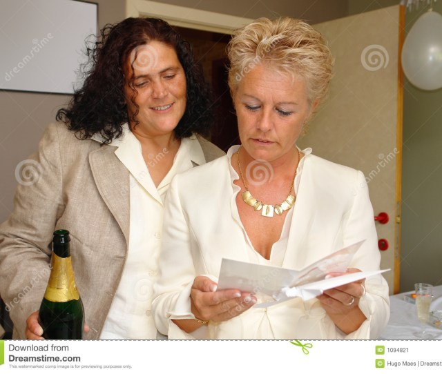 Just Married Happy Mature Lesbian Couple Reading Congratulations Or Greeting Card At Their Wedding Party