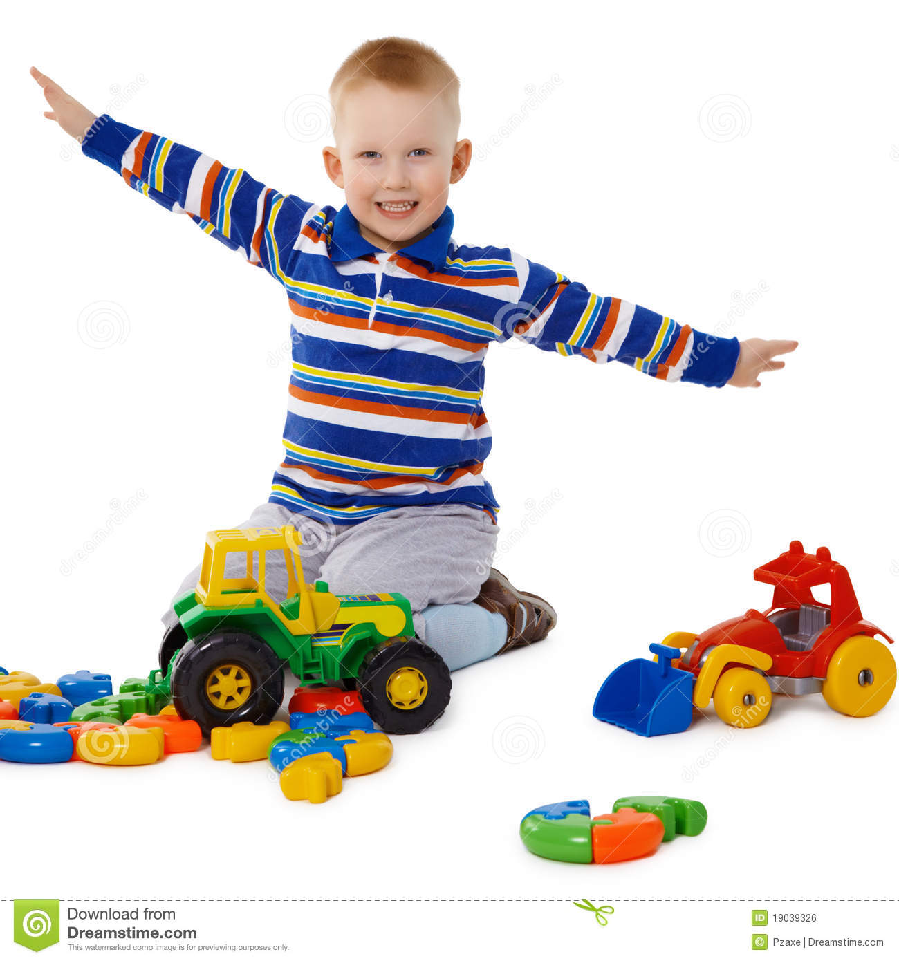 Little Boy Playing With Color Toys On Floor Stock Photo