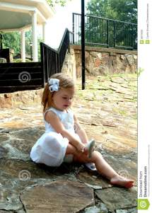 Little Girl Putting On Shoes