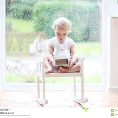 Little Girl Rocking Chair Doc Mcstuffins Saucer Reading In Front Of Big Window Stock Photo