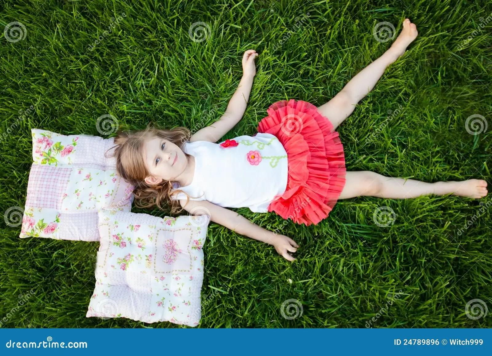 Little Girl Resting On Pillows In Summer Garden Stock
