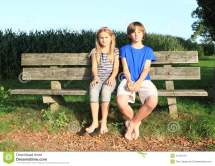 Little Kids - Girl And Boy Sitting Bench Stock