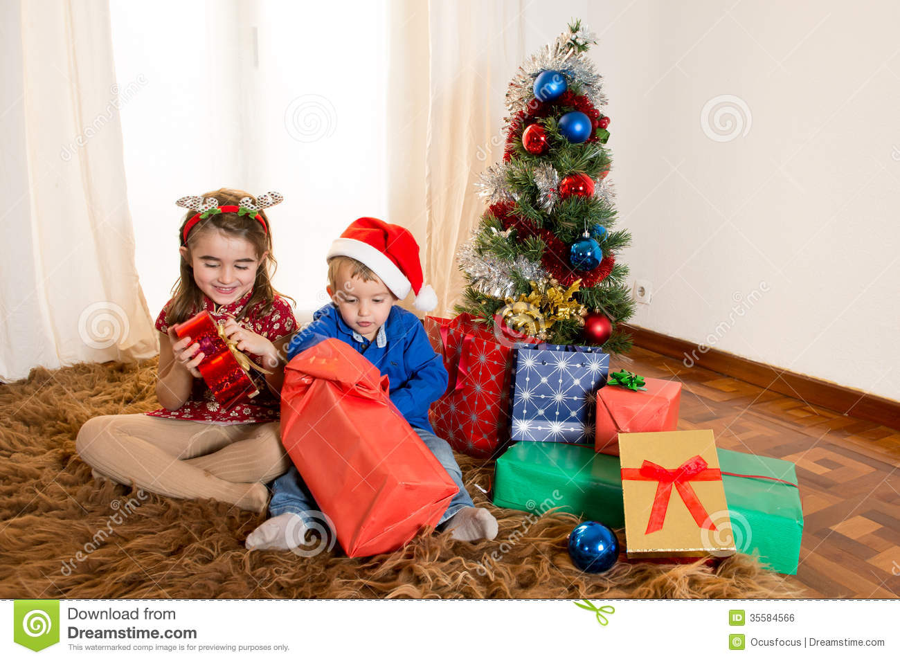 Little Kids On Rug Opening Christmas Presents Royalty Free