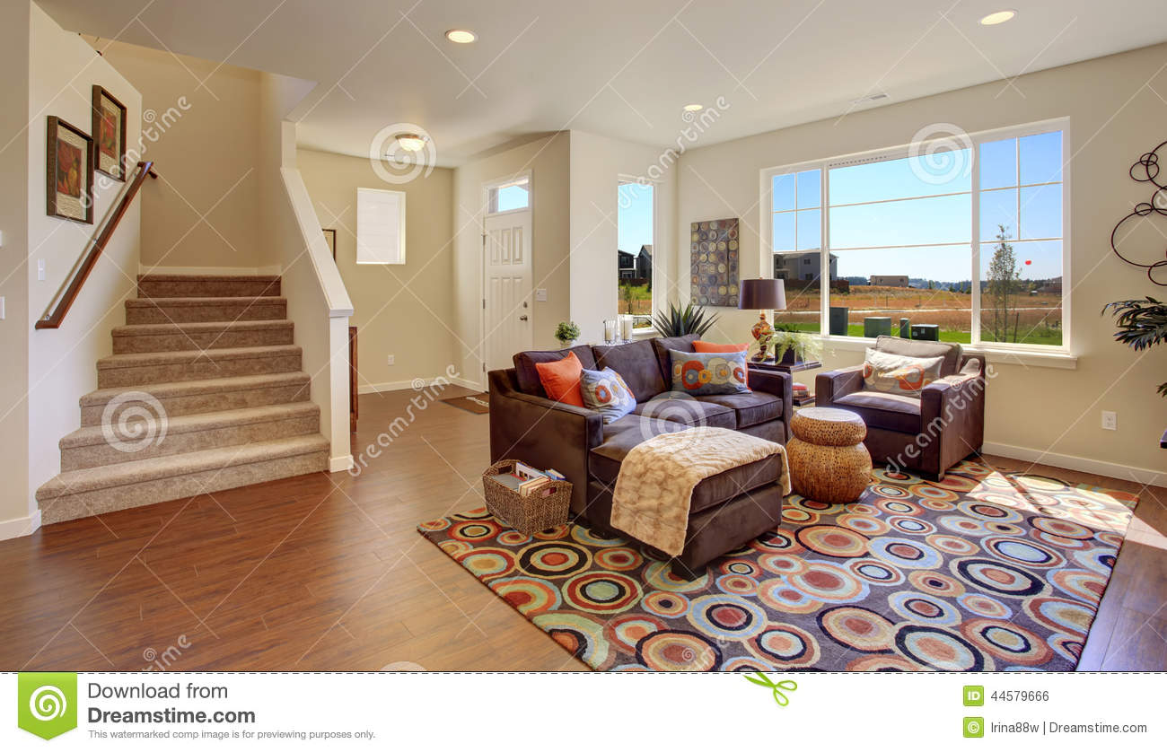 Living Room With Brown Couch And Cheerful Rug Stock Photo