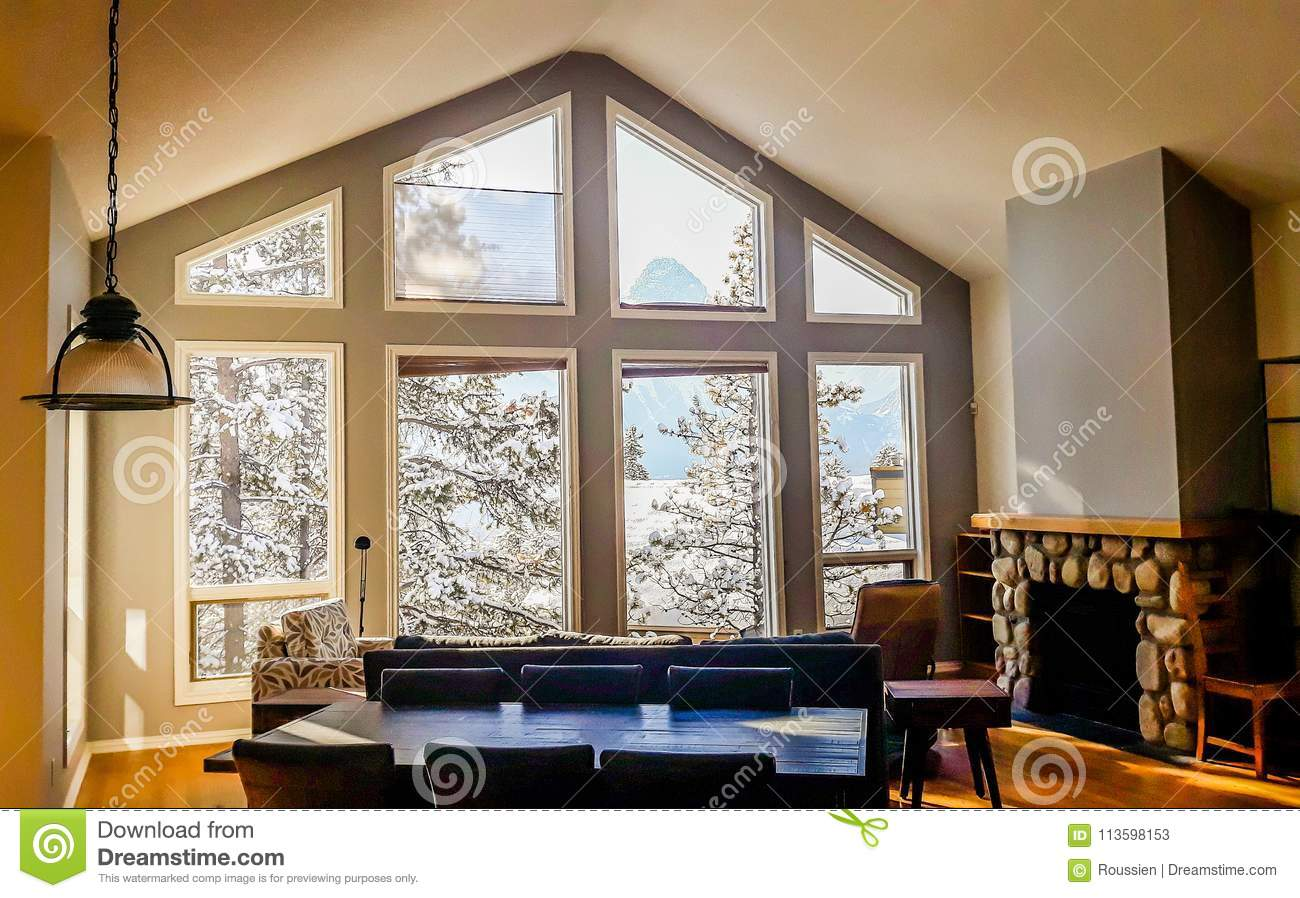 living room big window yellow walls with wide windows typical for mountain style in canada