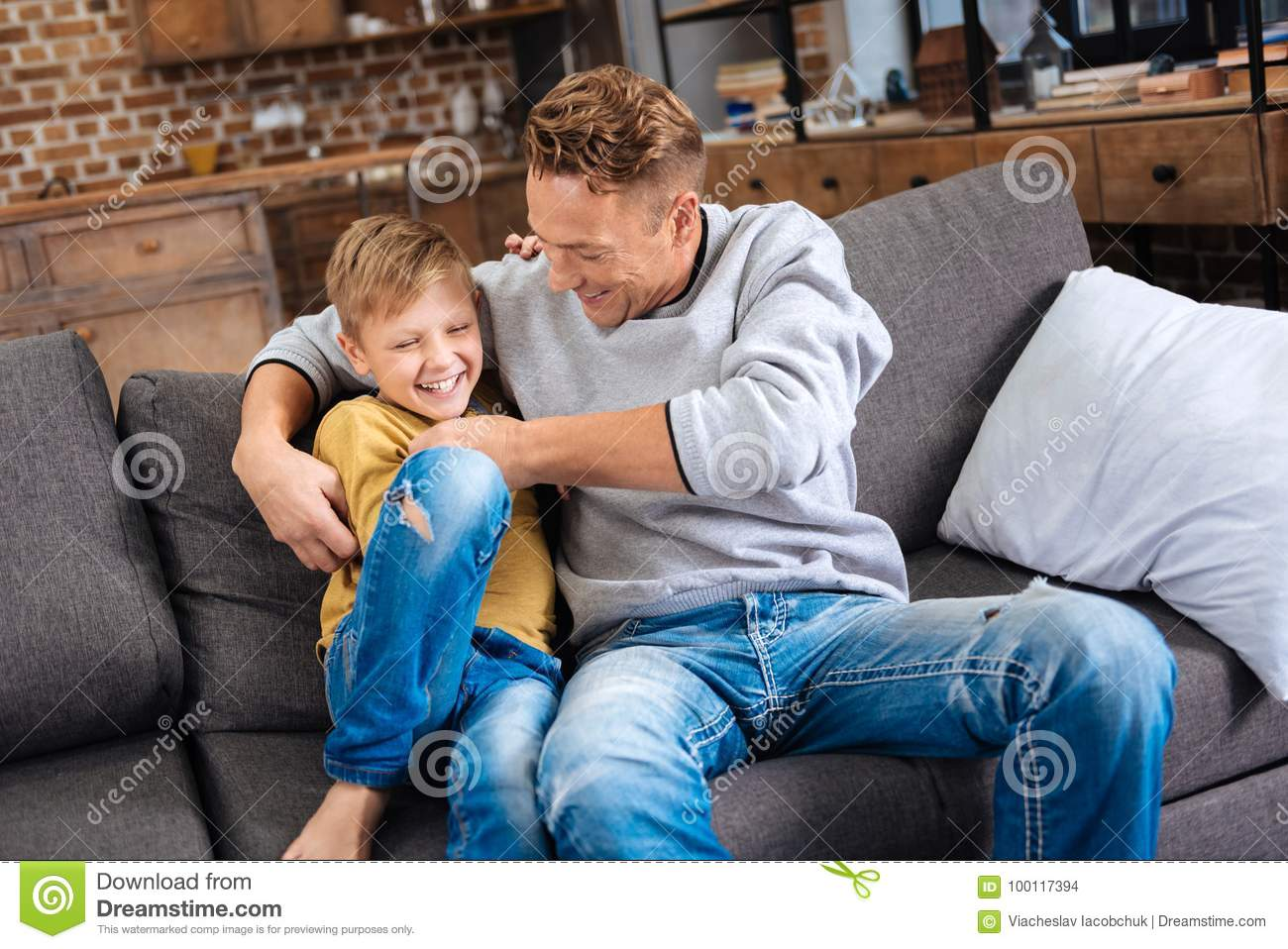 Loving Father Tickling His Little Son On Sofa Stock Photo