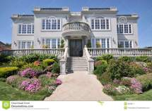 Majestic Two Story Mansion With Shrubs In Yard Stock