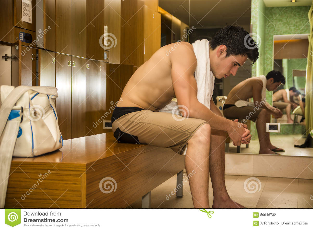 Male Athlete Resting On Bench In Gyms Locker Room Stock
