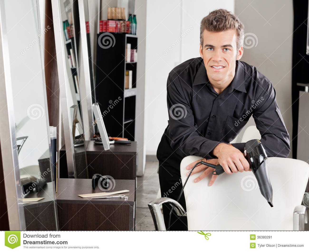 Male Hairstylist With Hairdryer Leaning On Chair Stock
