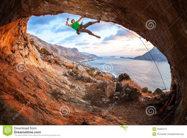 Male Rock Climber Climbing Roof In Cave Stock - 49483479
