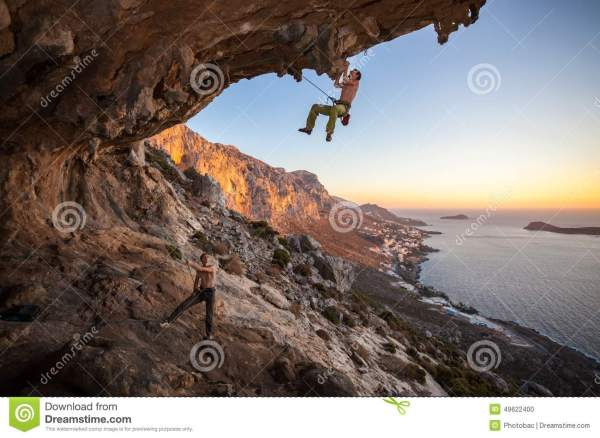 Male Rock Climber Climbing Roof In Cave Stock - 49622400