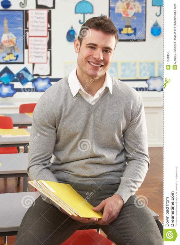 Male Teacher Sitting Desk In Classroom Royalty Free