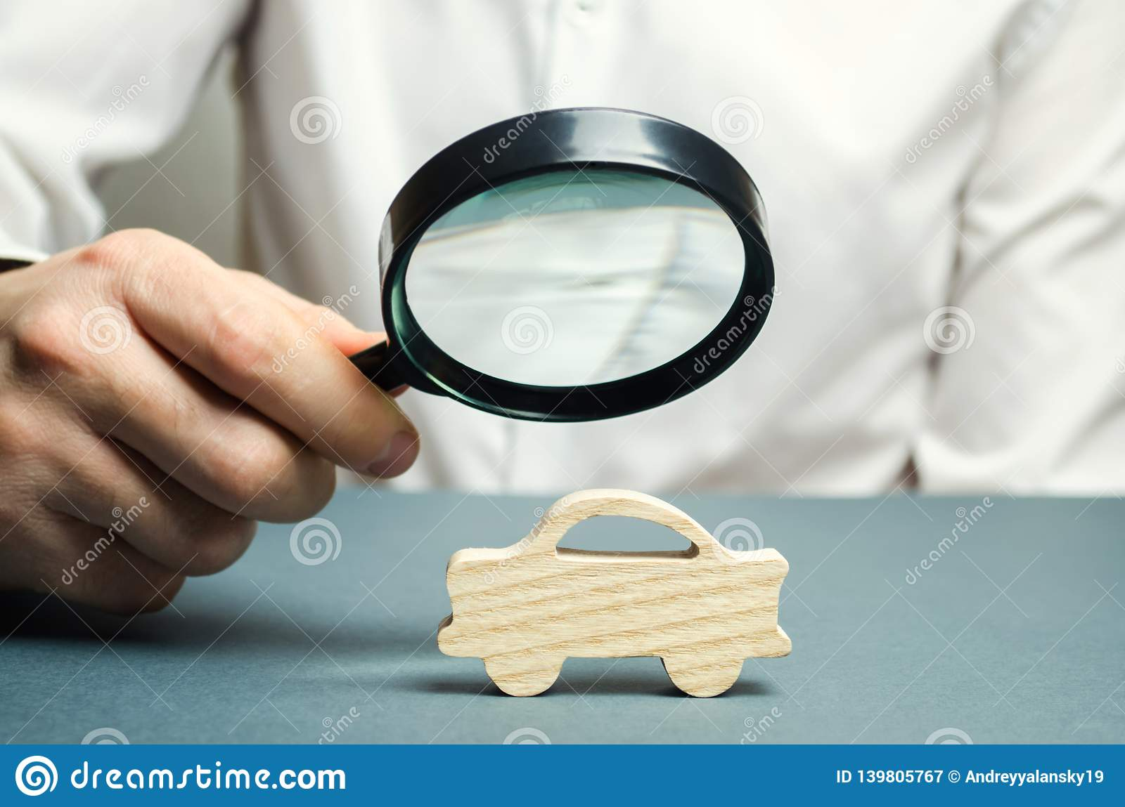 A Man Holds A Magnifying Glass Over A Miniature Wooden Car The Estimated Cost Of The Auto Analysis And Technical Inspection Of Stock Image Image Of Rent Inspection 139805767