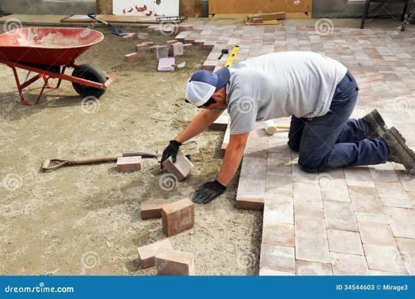 man laying paver stock