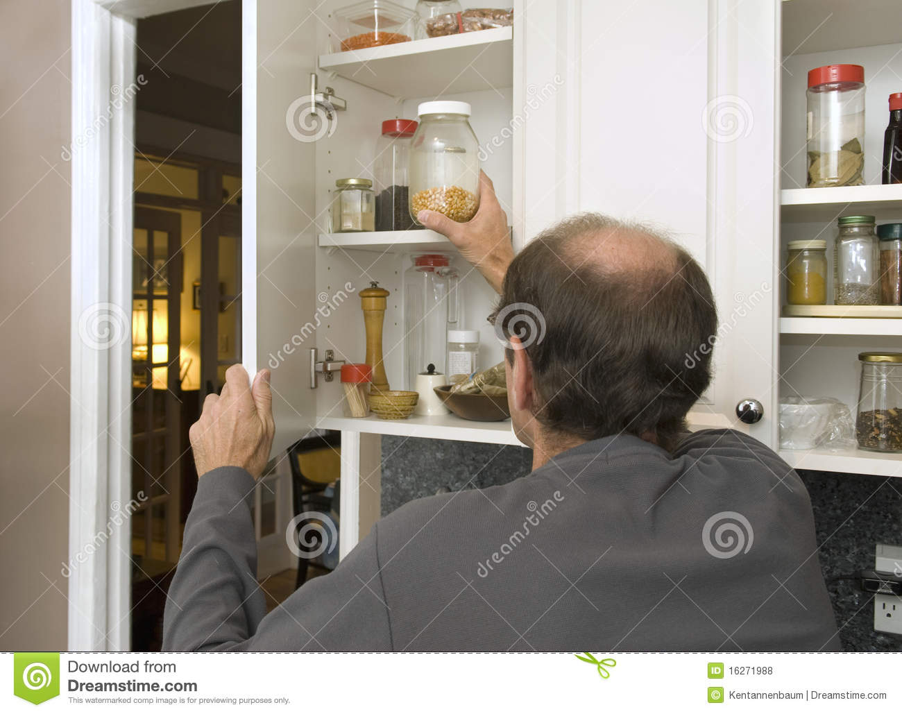 Man Reaching For Popcorn In Empty Cabinet Stock Photo